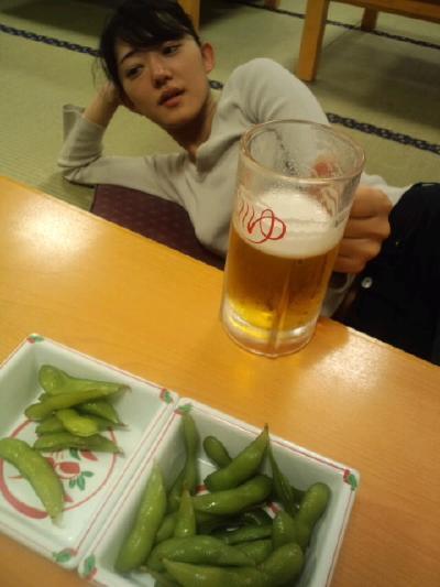 7枝豆を前に横たわりビールを飲む女性