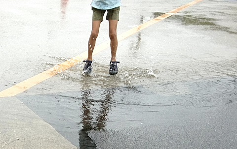 水たまりで遊ぶ小学生
