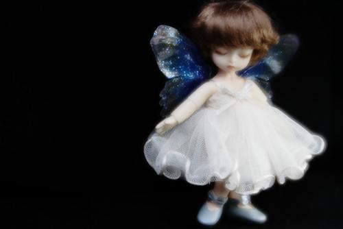DOLL FACTORY・Baby Ariの小さな眠り目の子、Emma(エマ)。妖精の羽をまとって、夜の暗がりの中で光り輝いている。
